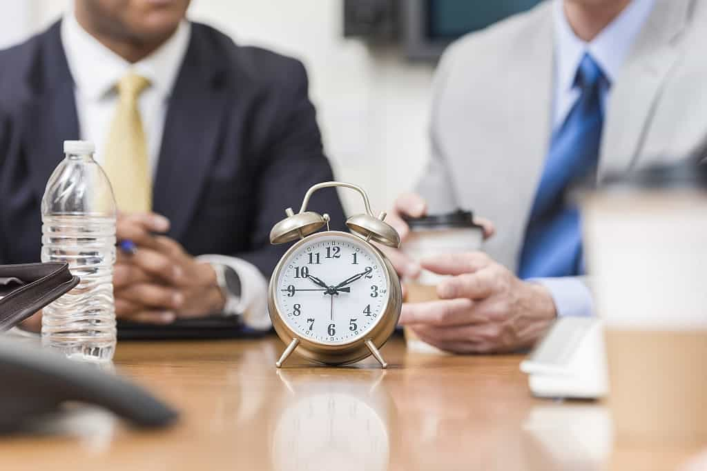Clock on table in front of businessmen